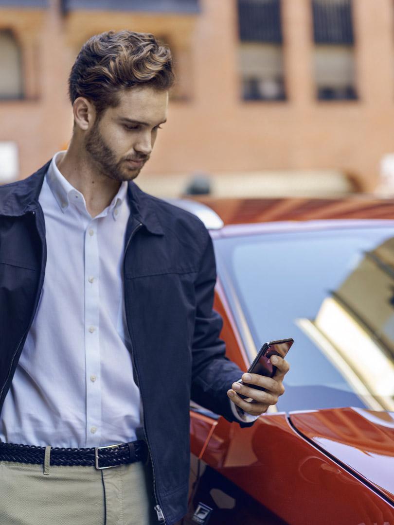 Junger Mann mit Smartphone vor Lexus UX Hybrid