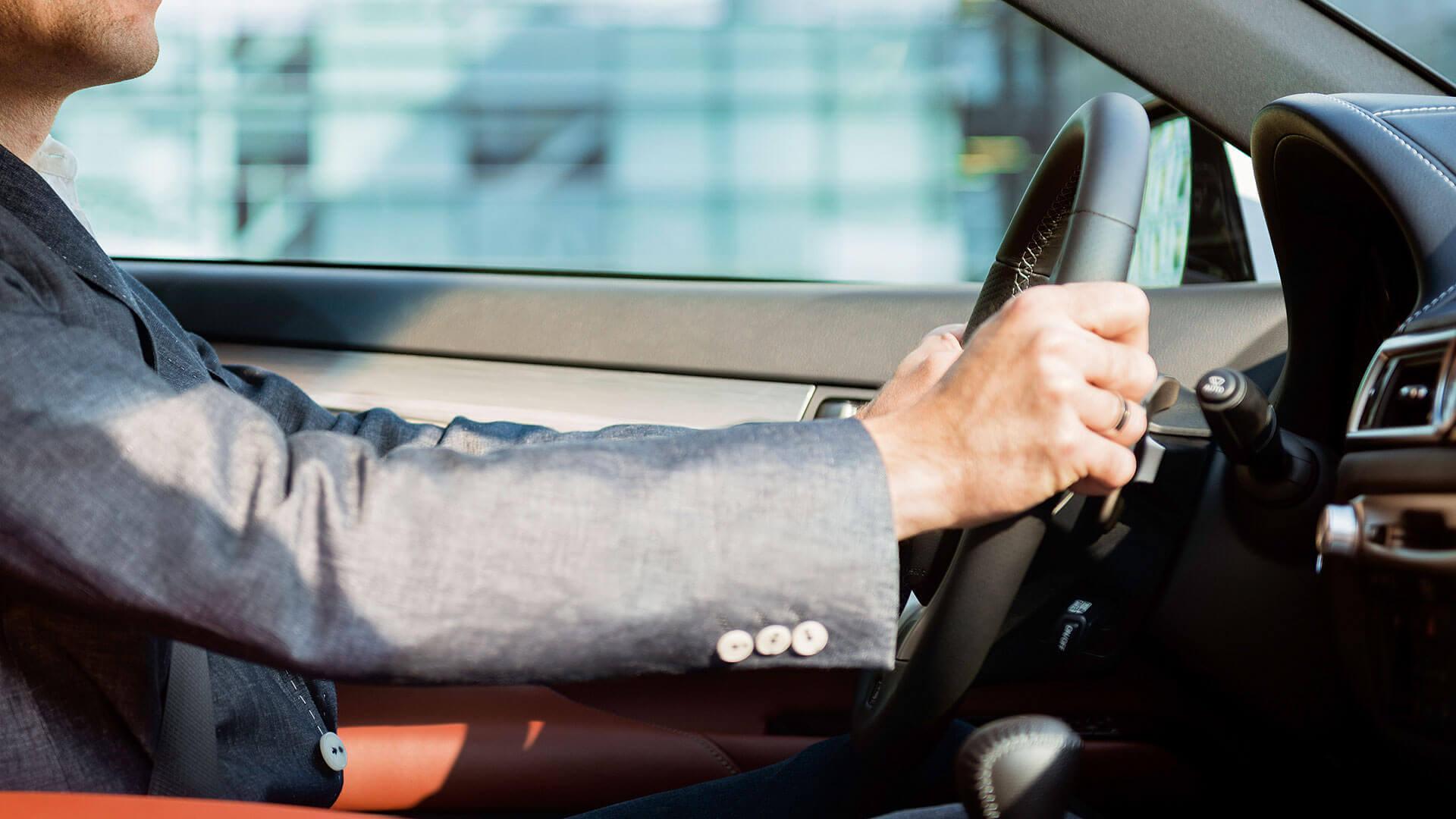 Man met een grijs pak in een Lexus CT 200h