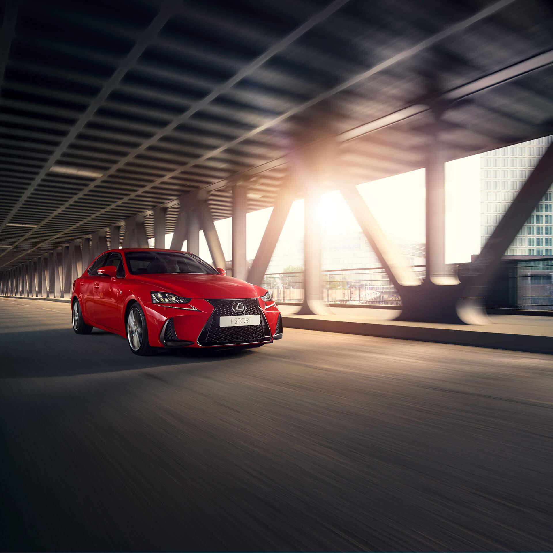 En rød Lexus F Sport kjører under en bru